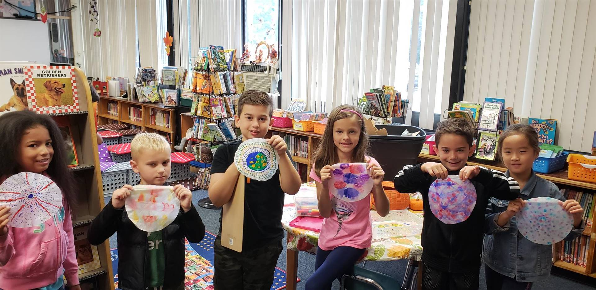 Students with Art they created in Library Class with Ms. Bronzino