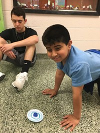Students Testing Spinning Top In Hallway