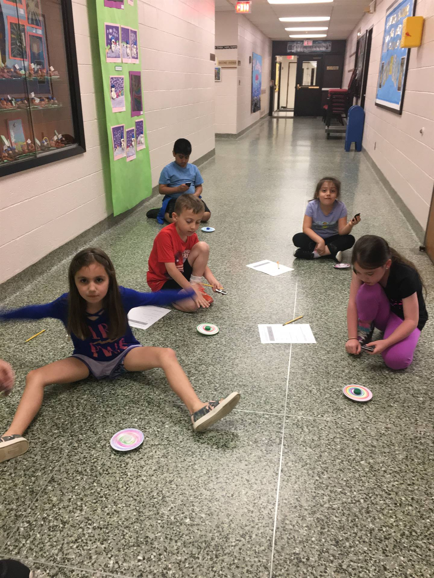 Students In Hallway Spinning Tops and Recording Data