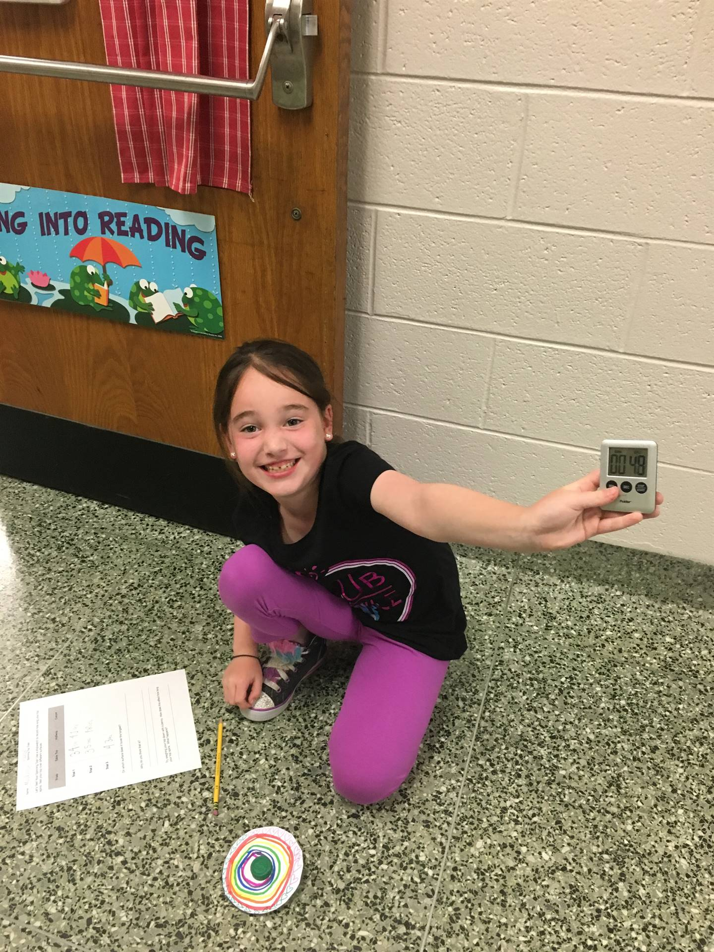 Student Showing Timer and Spinning Top