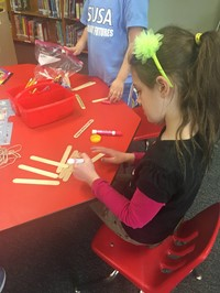Student Working With Tongue Depressors To Build Catapult